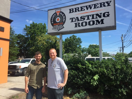 Chris Mazzone (left) and Chris Burke stand outside beneath the sign for Eight & Sand Beer Company's brewery and tasting room. The Woodbury brewery is celebrating its second anniversary.