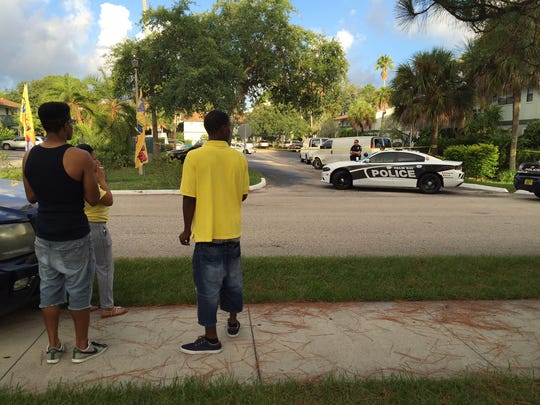 Bystanders look on Wednesday morning as investigators work the scene of a fatal overnight shooting in Palm Bay.