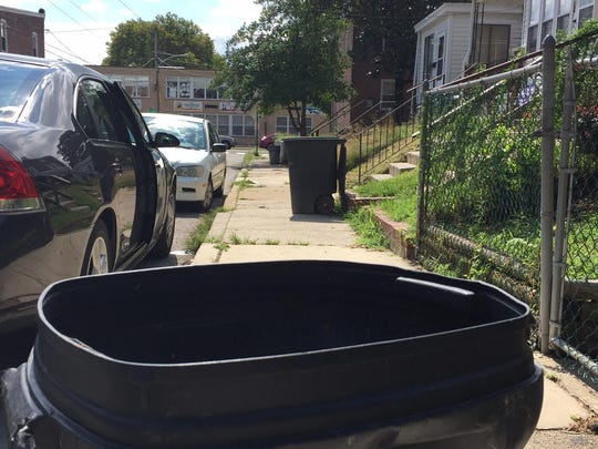 Garbage cans line the 800 block of East 22nd Street in Wilmington on Thursday. A woman's body was found in a trash container Wednesday.