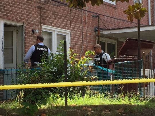 Police on Thursday search a home in Wilmington near where a woman's body was found in a trash can on Wednesday afternoon.