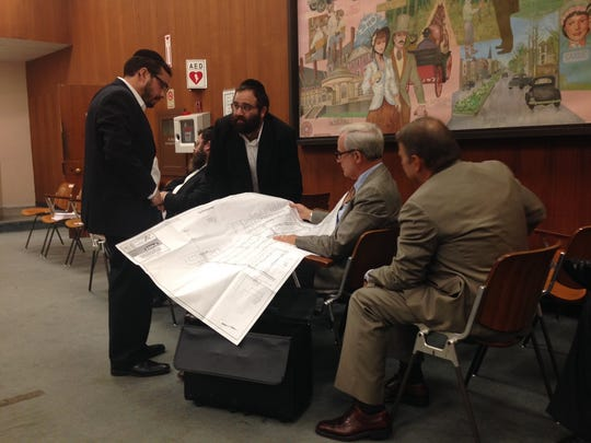 Developers and their attorneys huddle during public