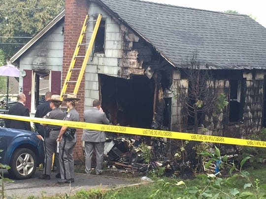 Officials inspect the damage after a house fire at