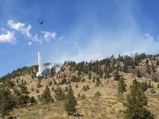 A helicopter drops water on the Starwood Fire northwest of Fort Collins.