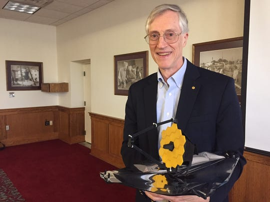 John Mather, a Nobel Laureate and senior project scientist for NASA's James Webb Space Telescope, holds a scale model of the observatory during a visit Thursday to the Florida Institute of Technology in Melbourne.