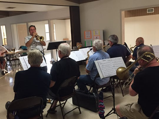 """Director James J. Milucky leads the first practice of the """"Band of the Bay."""""""