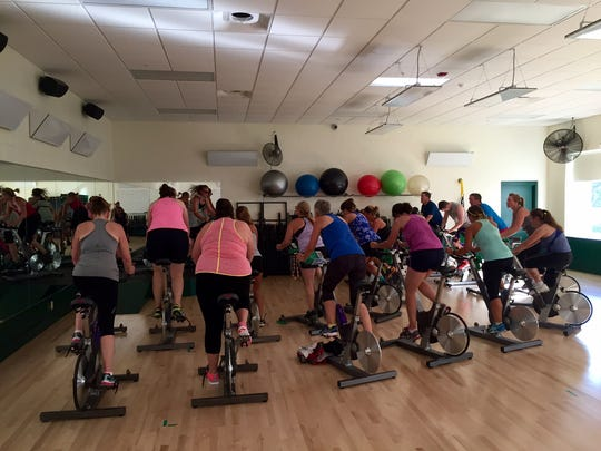 Participants in an RPM class work out on stationary bicycles.