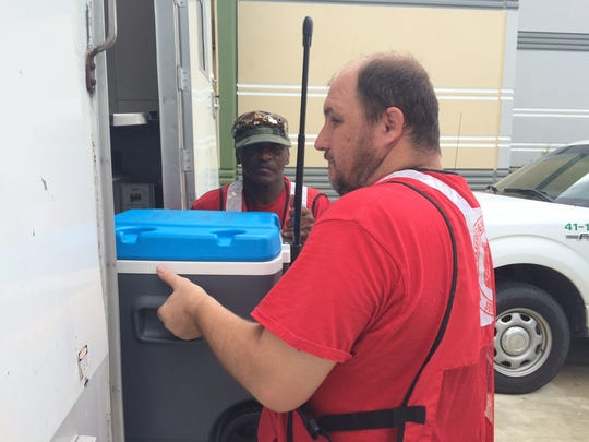 Roy Brooks, left, and Mike Taylor unload supplies to feed first-responders at St. Lucie County Emerggency Opeerations Center
