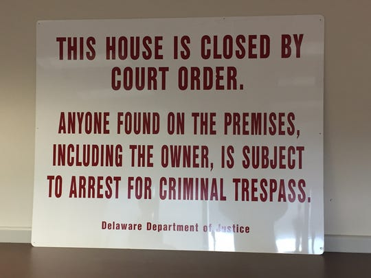 A sign the Delaware Department of Justice uses to warn people that a property is the subject of court action under the criminal nuisance abatement statute is shown Thursday. The Delaware Department of Justice announced Thursday that it has targeted nine properties through formal court complaints in the last year.