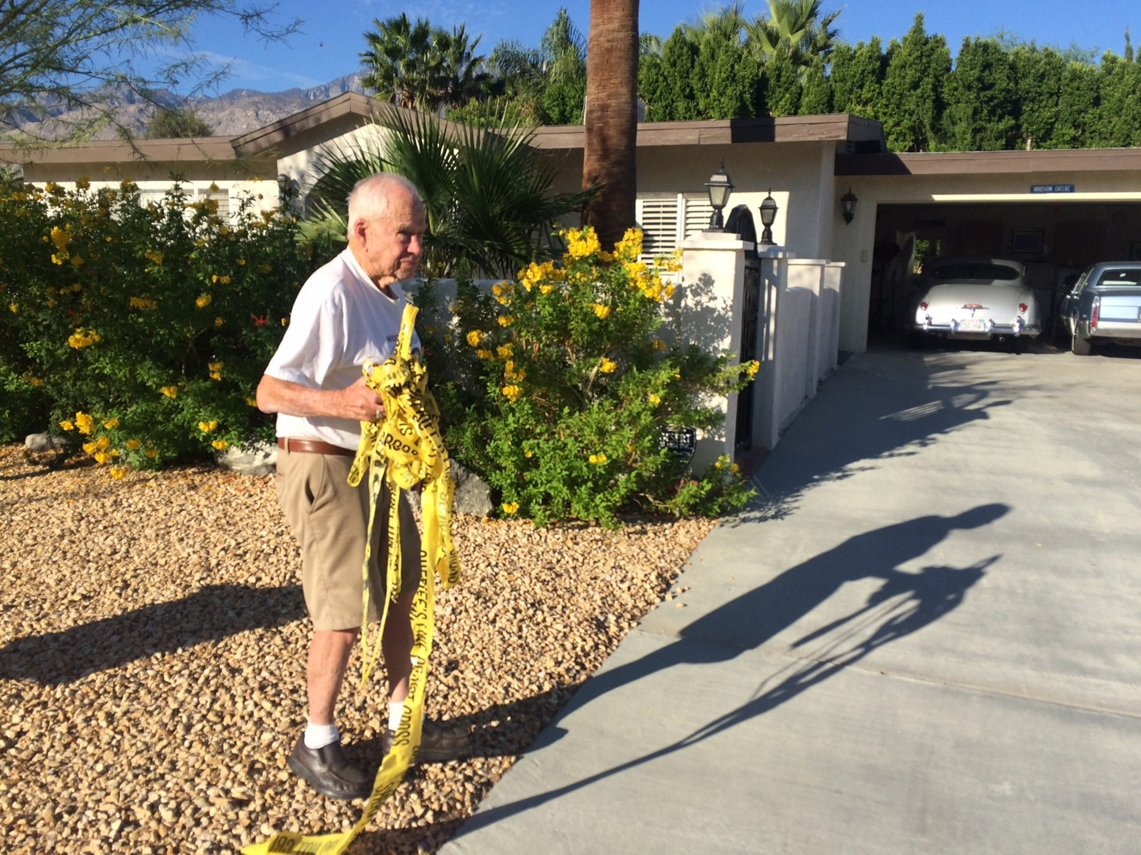 Fred Elg, 93, picks up handfuls of police tape left in his yard by police following a shooting Saturday that left two Palm Springs police officers dead and wounded a third.