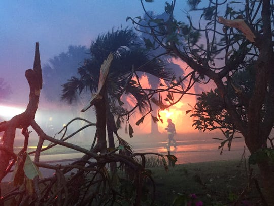 Seen through snapped branches across the street, a Satellite Beach home burned down during Hurricane Matthew.