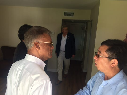 At right, Li Jianxiang, executive project manager for construction for TPCO America, speaks with general contractor George Thomas, left. TPCO America held an open house for its employee apartments in Portland. The complex once was rundown housing until it was purchased and remodeled by the Chinese pipe manufacturer, which is building a $1 billion plant in nearby Gregory. Thomas, a contractor, completed most of the renovations at the apartment complex. Portland mayor David Krebs is at center.