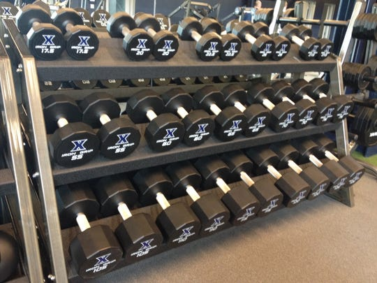 New free weights in Xavier's strength and conditioning facility have custom logos.