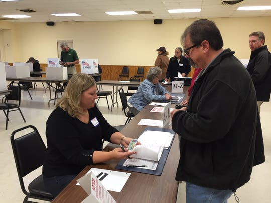 Just after the polls opened at 6 a.m., poll worker Christina Gronick signs in voter Michael Brauer, of Bellevue, at the Bellevue Vets polling location on Nov. 8.