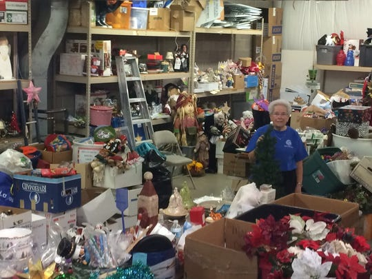Volunteer Mary Jo Ragaller of Ankeny is nearly lost in decorations she stacks for 11 months each year at St. Vincent de Paul.