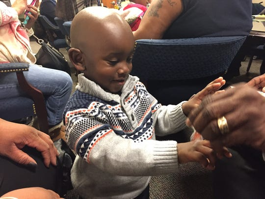 Tymir Brewer, 2, was too happy playing with stickers to even realize how special Tuesday was for him. Tymir and was adopted by his cousin Ieshia Brewer, who has raised him since he was two weeks old. Now officially mother and son, the Brewers were one of  15 families who welcomed 18 new members as long-awaited adoptions were finalized during National Adoption Day at the Middlesex County Courthouse Tuesday.