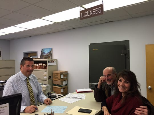 Gloria and Ed Schuetz, right, prepare a subsequent marriage certificate with the help of Gates Town Clerk Cosmo Giunta.
