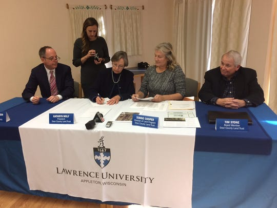 The agreement was signed by Lawrence University president Mark Burstein (left); Kathryn Wolff, president of the Door County Land Trust (third from the left); Terrie Cooper, director of land program for the Land Trust; and Tim Stone, Land Trust Board member. Also pictured is Jacquie Birkholz a notary from Lawrence University (second from the left).