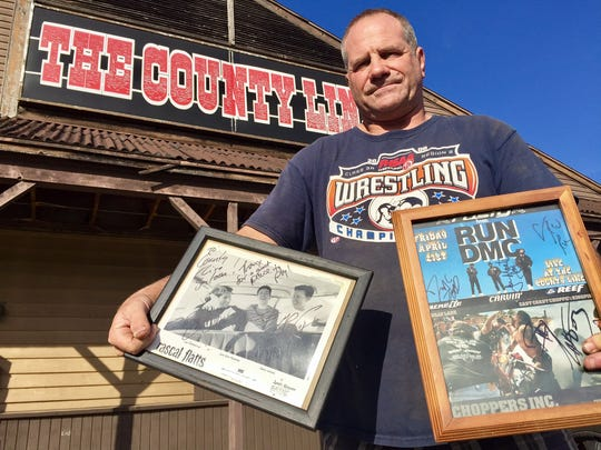 County Line Saloon owner Kelly Benninger holds framed autographed photos of Rascal Flatts and Run DMC outside his former nightclub after it closed in December 2016.