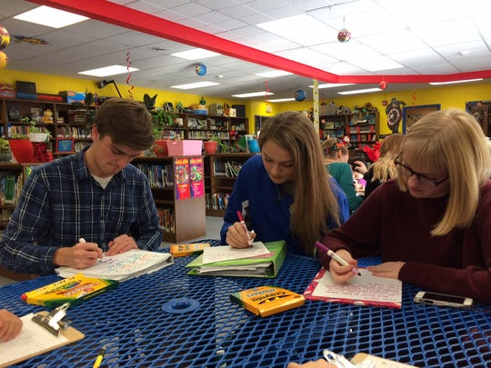 Gibraltar High School seniors Topher Andersen, Sheridan Ash and Elizabeth Henry work on letters to Santa for Macy's Make-A-Wish fundraiser.