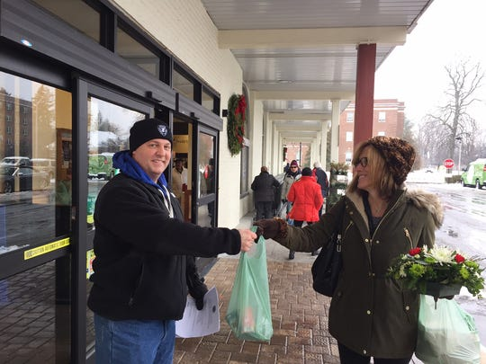 Morristown Police Officer Brendan Murphy accepts a bag of food from Kings Food Market shopper Jennifer Willette that will be donated to the Interfaith Food Pantry.
