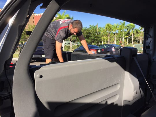 Shawn Metcalfe of Mike's Auto Glass works on replacing a back window on a Ford F150 that was smashed in a string of car burglaries Christmas morning in 2016.