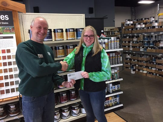 Jim Lenselink presents a donation to Molly Lewandowski for Peyton's Promise. Hallman Lindsay celebrated its 60th year by giving $30,000 to 60 food pantries in Wisconsin.
