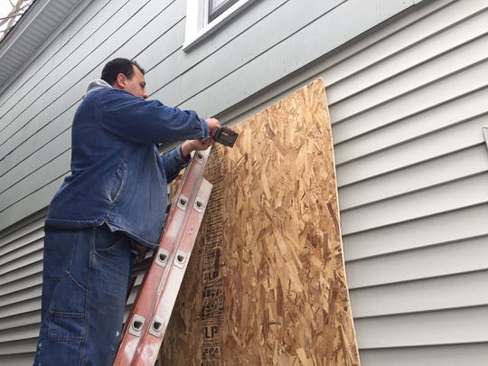 Rony Santico, who owns the vacant house at 97 Smith Street, installs a new plywood board over a window. He also came over Saturday night to do the front and back doors.