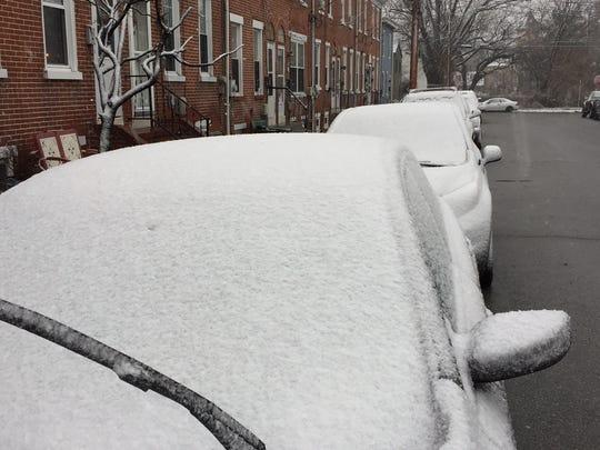 Snow accumulates on cars near New Castle.