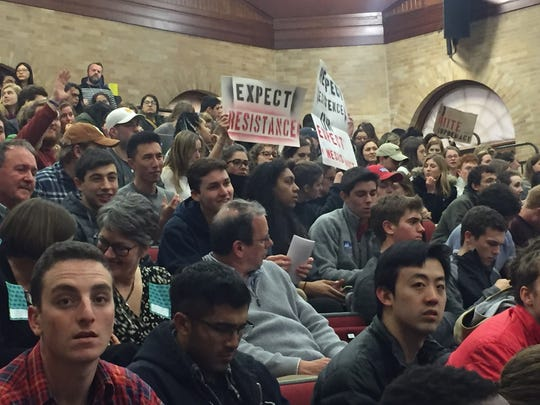 Students wave signs in protest of Dr. Charles Murray's speech on Thursday.