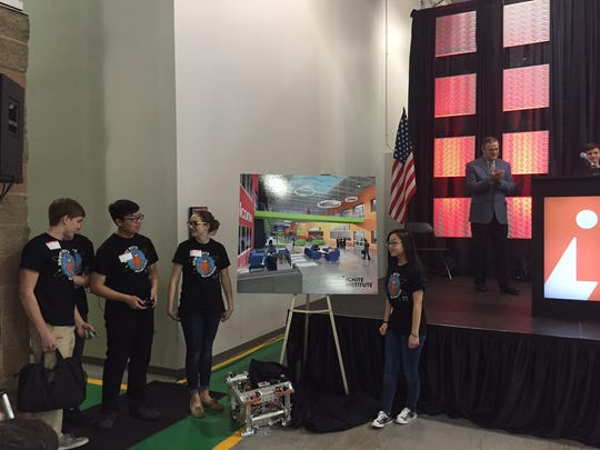 Ryle High School students Tanner Schmidt, Ken Ryumae and Gray Middle School students Kate Grayson and Mina Ryumae, and their robot 8913 unveil a rendering of the Ignite Institute.