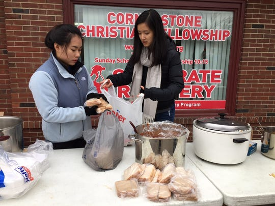 Grace Zhang (right) and Vivian Guo bag food for visitors