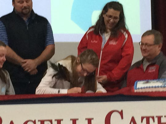Pacelli senior Christonna Shafranski is surrounded by family and coaches as she signed a letter-of-intent with Upper Iowa University at the school on Wednesday morning. She will run cross country and play softball for the Peacocks.