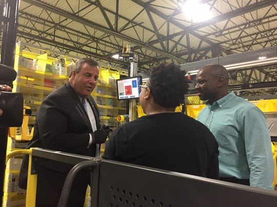 Gov. Chris Christie chats with a worker during Friday's tour of the Amazon Carteret Fulfillment Center.