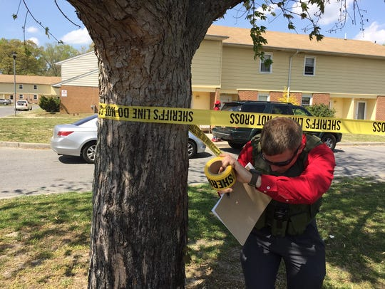A member of the sheriff's office wraps police tape