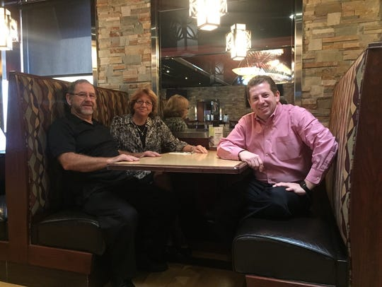 Angelo and Antonia Kyrtatas and their son, George Kyrtatas, sit in a booth at the family's SweetWater Bar & Grill in Cinnaminson. The restaurant welcomes families and offers free meals for kids on Mondays with the purchase of an adult entree.