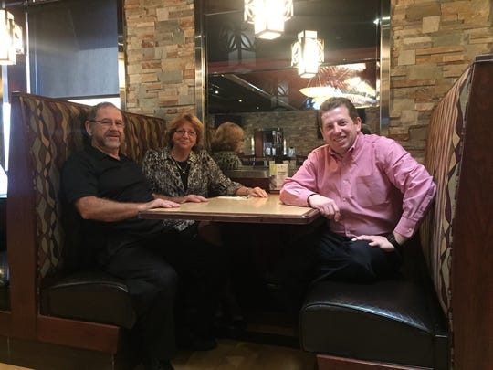 Angelo and Antonia Kyrtatas and their son, George Kyrtatas, sit in a booth at the family's SweetWater Bar & Grill in Cinnaminson. The family has been in the restaurant business in this town for 32 years.