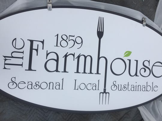 Fresh out of its bag, the new sign is about to be installed Monday at The Farmhouse in Cherry Hill.