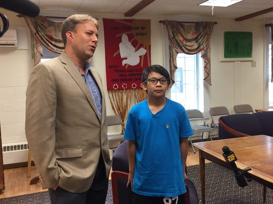 The Rev. Seth Kaper-Dale, pastor of The Reformed Church of Highland Park, with Joel, 13, the son of Arino Massie, an ethnic Chinese Christian man who was deported to Indonesia on Thursday.