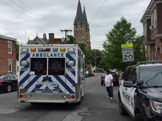 An ambulance takes someone away from the scene at Elm Street on Wednesday morning in Wilmington.