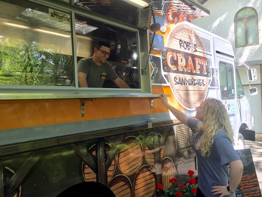 Rob and Kim Silcox chat through the window of their food truck, Rob's Craft Sandwiches, in their Medford driveway. Look for the truck at area food truck fests.
