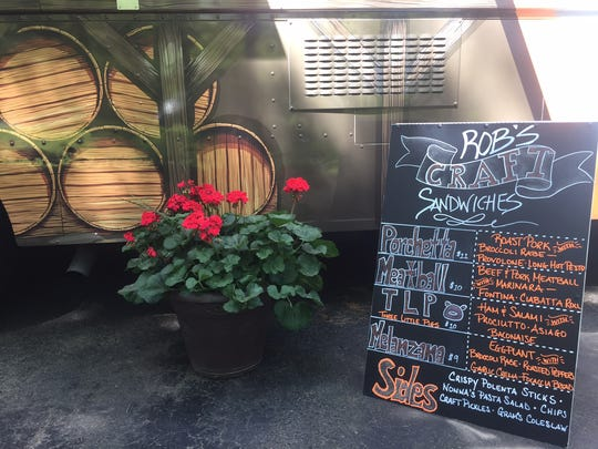 A menu of sandwich options sits beside Rob's Craft Sandwiches food truck. The truck's theme and design is meant to pair well with New Jersey craft breweries.