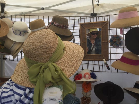 A patron at the Chester Craft Show admires a sun hat