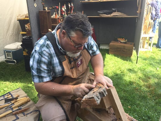 Wood carver Mark Bair demonstrates his skill at the