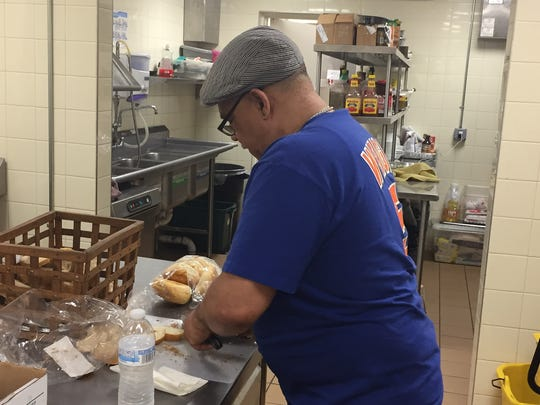 Michael Williams, chef at Table of Hope at Bethel Church of Morristown, breaks bread for dinner on June 8, 2017.