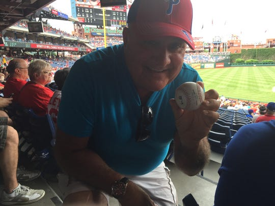 Cherry Hill Township bus driver Tom Bush holds the foul ball he grabbed at a Philadelphia Phillies game on June 4. Bush treated one of his longtime passengers, 92-year-old Ida Geltzer, to her very first Phillies game. The Gloucester City resident snagged the ball and gave it to Geltzer. He also took one of her friends to the game as well.