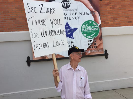 Jerry O'Neil holds a sign in support of the Interior