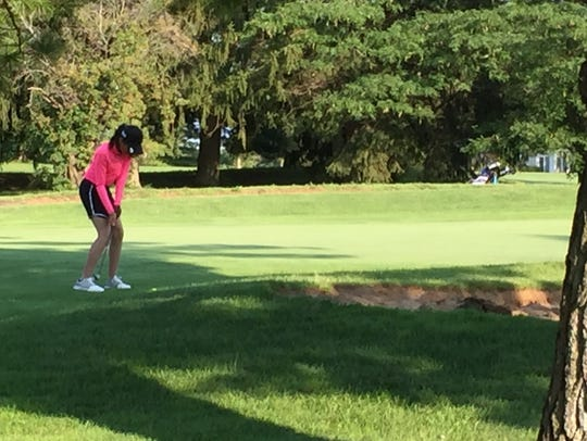 Dina Shaw takes a putt on the par-3 fifth hole at the