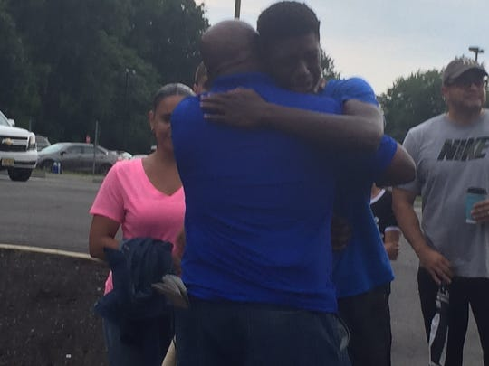 North Brunswick Township High School student Ahmad Kargbo was consoled by those who attended the vigil for his brother at North Brunswick High School stadium on Monday night.