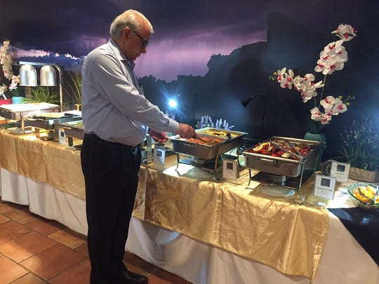 Rewal Thind stirs a steaming buffet tray ahead of the lunch seating at Monsoon Fine Indian Buffett in Cherry Hill.