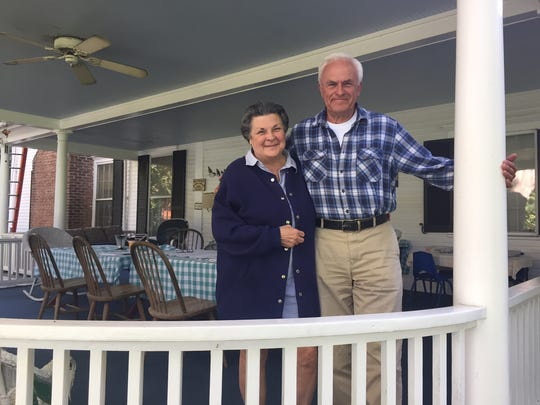 Betsy and Roger Powers on the porch of their home on their Pittsford farm.